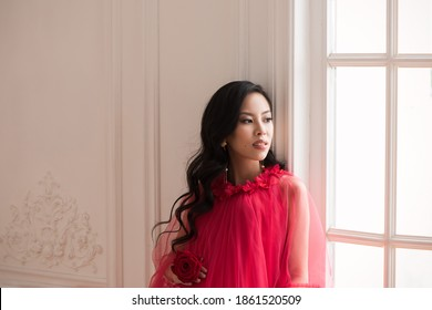 Beautiful asian pregnant woman in long red dress indoors