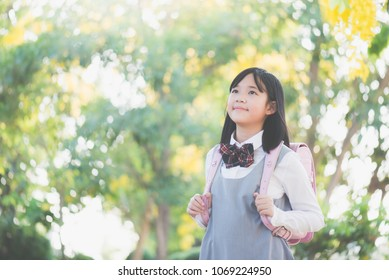 Beautiful Asian school girl with pink backpack looking up outdoors,back to school concept