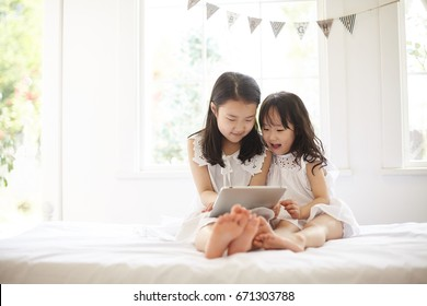 Beautiful asian sisters using tablet while lying on bed