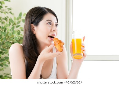 beautiful asian smile woman eating croissant and holding orange juice, healthy food concept indoor background