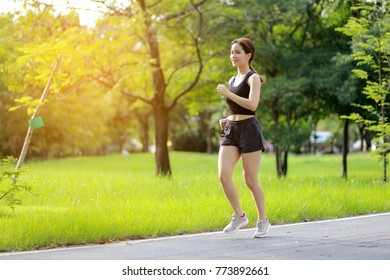 Beautiful asian sport girl running at outdoor park with happy feeling.