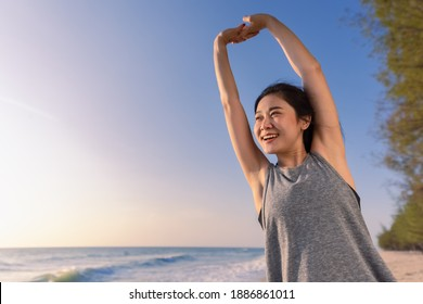 Beautiful Asian sporty girl smiling stretching hands warmup for running on beach in morning