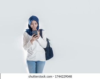 Beautiful Asian student in hijab surprised while looking at a mobile phone