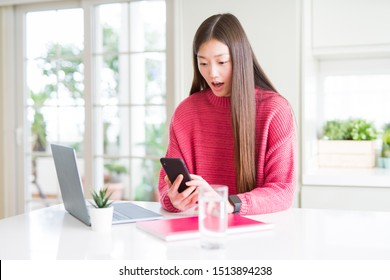 Beautiful Asian student woman using laptop and smartphone scared in shock with a surprise face, afraid and excited with fear expression