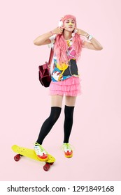 A beautiful Asian teen girl in pink headphones, dressed in anime or kawaii style, with a skateboard and backpack, holding a lollipop. On a pink background.