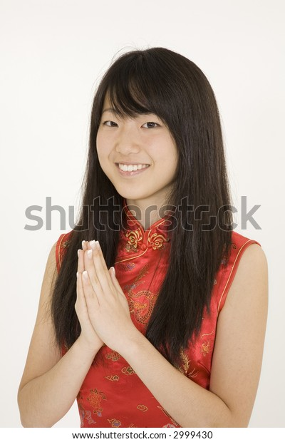 Beautiful Asian teenager in traditional dress on white background