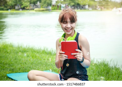 Beautiful Asian teenagers like to exercise, wear headphones, hold tablets, sit by the pool in the park.