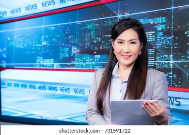 Beautiful Asian television newscaster at broadcast room
