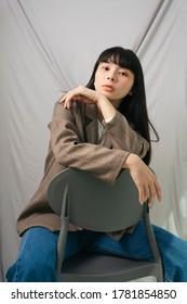 Schöne asiatische thailändische lange dunkle Haare Frau in Jackenanzug und Jeans Hosen sitzen auf Stuhl. Modeporträt.