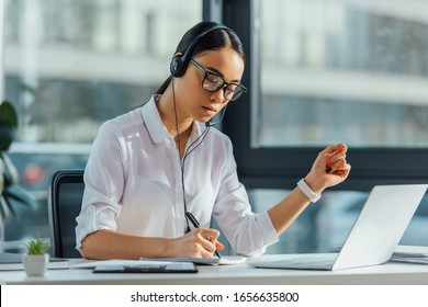 beautiful asian translator working online with headset and laptop in office