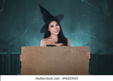 Beautiful asian witch woman with empty banner for copyspace