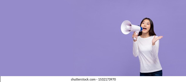 Beautiful Asian woman announcing on magaphone isolated on purple banner background with copy space