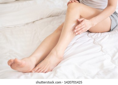 Beautiful Asian woman applying body lotion on her legs and sitting on her bed.