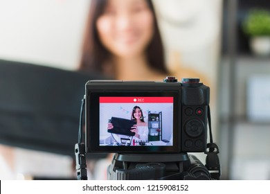 Beautiful asian woman blogger is showing cosmetic bag. In front of the camera to recording vlog video live streaming at home.Business online influencer on social media concept.
