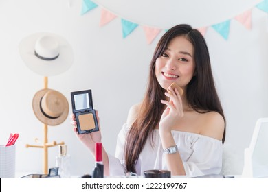 Beautiful asian woman blogger is showing how to make up and use cosmetics. In front of the camera to recording vlog video live streaming at home.Business online influencer on social media concept.