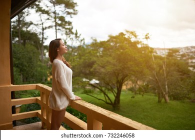 Beautiful Asian woman breathing fresh air on villa balcony in morning