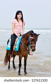 beautiful asian woman with brown horse on beach
