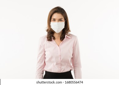 Beautiful Asian woman in casual business dress wearing surgical hygiene protect mask on white background and looking at camera. Idea for prevention from coronavirus outbreak and safe in pollution air.