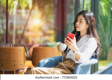 A beautiful Asian woman close her eyes and listening to music with headphone while drinking coffee with feeling happy and relax in cafe