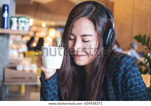 A beautiful Asian woman close her eyes and listening to music with headphone while drinking coffee with feeling happy and relax in modern cafe