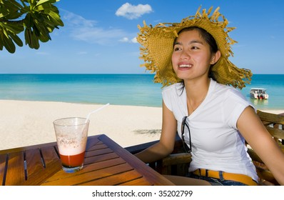 beautiful asian woman with cocktail at the beach