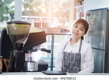 Beautiful Asian woman coffee barista using coffee machine in counter. Successful small business owner standing entrepreneur or entrepreneurship
