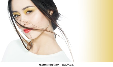 Beautiful Asian woman with colorful soft makeup with yellow and orange tones.