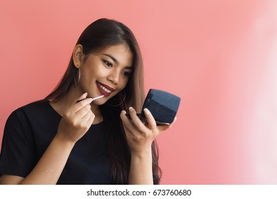 Beautiful Asian woman with cosmetic over pink background