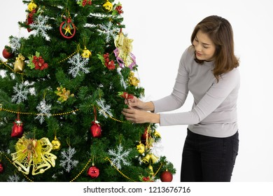 Beautiful Asian woman decorating her hugh christmas tree with lots of luxury decorations her face shows she is happy and ready for the celebration of christmas. The background with copyspace.