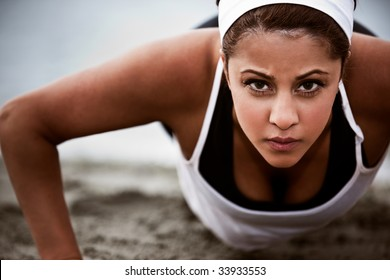 A beautiful asian woman doing push up at a beach