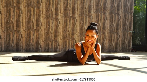 Beautiful Asian woman doing the split on the floor, smiling