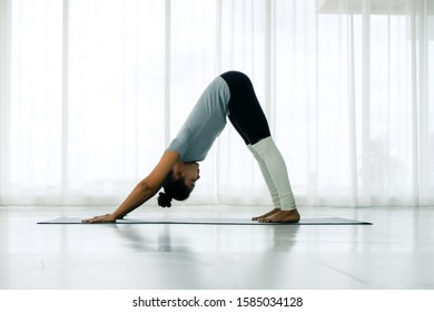 Beautiful Asian woman doing yoga exercise in the white room, downward facing dog pose, adho mukha svanasana (sun salutation pose), full length, Concept of healing body and spirit.side view