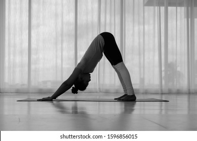 Beautiful Asian woman doing yoga exercise in the white room, downward facing dog pose, adho mukha svanasana (sun salutation pose),full length, Concept of healing body and spirit.side view,monochrome