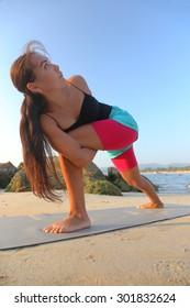 Beautiful asian woman doing yoga on the beach