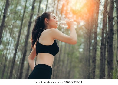 Beautiful asian woman drinking cool water bottle in the spruce forest nature for relaxing after runner exercise cardio workout or loss of sweat recovery refreshment active healthy lifestyle