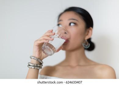 Beautiful asian woman drinking a glass of water.