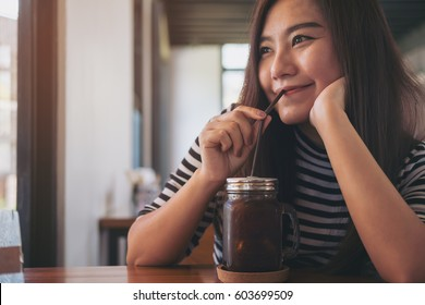 A beautiful Asian woman drinking iced coffee with straw in modern cafe