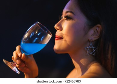 Beautiful asian woman drinking wine alcohol in restaurant. concept of night party, celebration, happy new year and lady night.