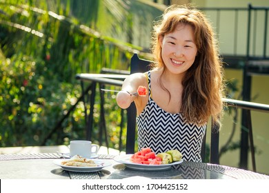 beautiful asian woman eating breakfast at tropical resort.she is drinks cup of tea or coffee