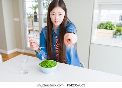 Beautiful Asian woman eating fresh green peas pointing with finger to the camera and to you, hand sign, positive and confident gesture from the front