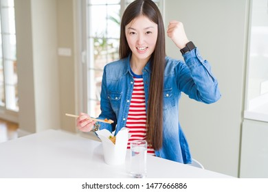 Beautiful Asian woman eating asian rice in delivery box annoyed and frustrated shouting with anger, crazy and yelling with raised hand, anger concept