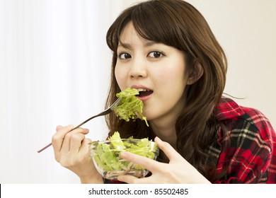 Beautiful asian woman eating salads