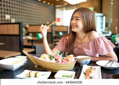 Beautiful asian woman eating sashimi, Japanese food.