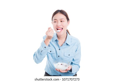Beautiful asian woman eating yogurt with fruits over white background
