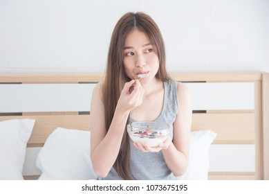 Beautiful asian woman eating yogurt with fruits for breakfast