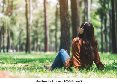 A beautiful asian woman enjoy listening to music with headphone with feeling happy and relaxed in the park - Shutterstock ID 1455833660