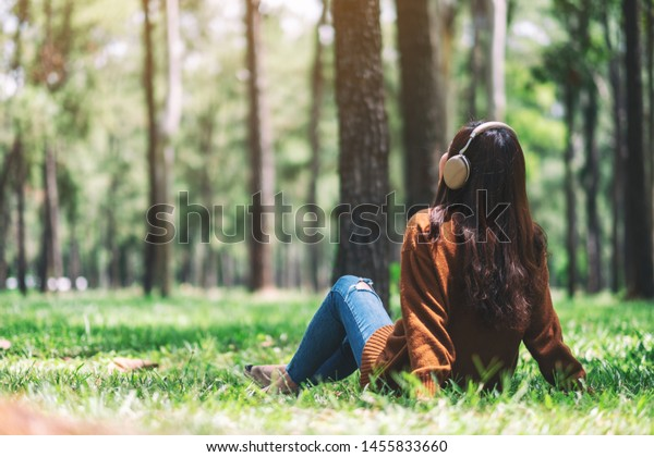 A beautiful asian woman enjoy listening to music with headphone with feeling happy and relaxed in the park