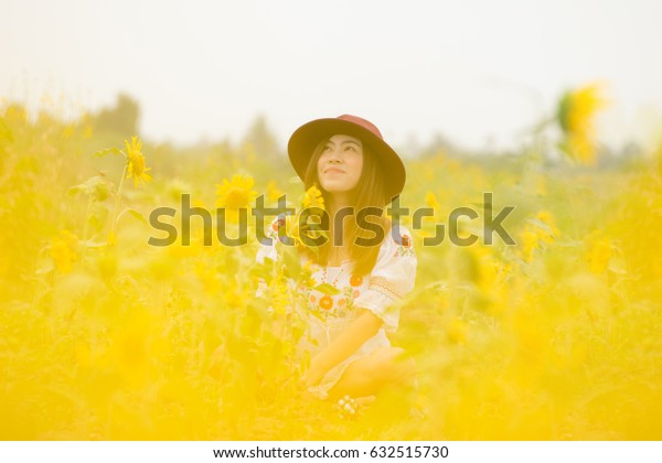 Beautiful Asian woman is enjoy travel in to Sunflower field.