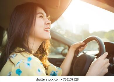 Beautiful asian woman enjoying life  in the red car.