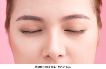 Beautiful asian woman eye with long eyelashes isolated on pink background.
